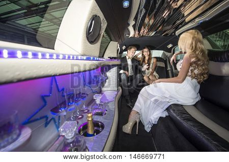 Three rich and famous people, celebrities, sitting in a luxurious limousine, chatting away, having a good time.