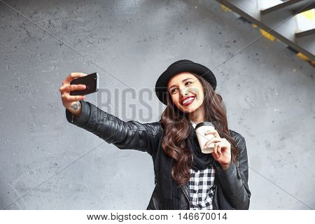 Pretty Hipster Girl With Red Lips And In Hat Taking Selfie In The Street. Sending Kisses And Holding