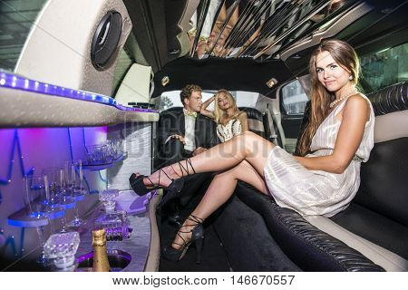 Pretty woman in a short dress sitting on a comforable sofa inside a luxurious limousine, with a couple of rich and famous Celebrities in the back seat of the car