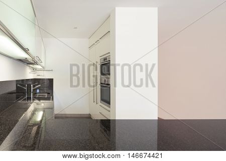 Interior of empty apartment, domestic kitchen, counter top black marble