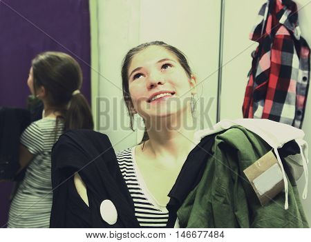 teen girl with brand new clothes in fitting room