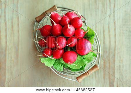 Fresh radish in basket on wooden table