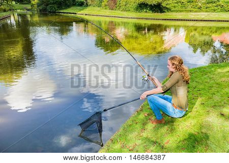 Young caucasian woman at waterside with fishing rod and landing net