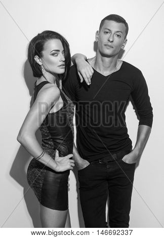 Black and white photo of elegant sexy couple in posing, standing against wall