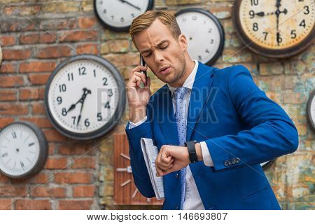 I think someone late. Businessman making phone call and checking time while sitting outdoor with brick wall on background