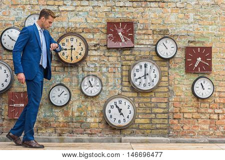 He is always on time. Young man in blue suit walking along brick wall and checking time on his smartwatch