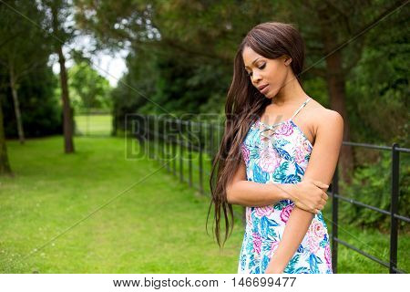 thoughtful woman in a summer dress outdoors.