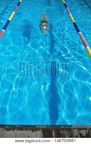 Active girl swims in the swimming pool. Swimmer wears a black-lime swimsuit, a white swim cap and swim glasses. Her face is under water. Shoot from the top. Outdoors. Vertical.