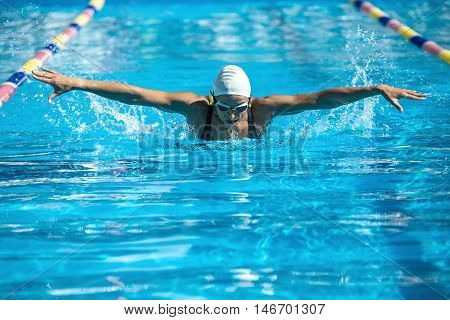 Energetic female swimmer swims in the butterfly style in the swimming pool. Woman wears a black-lime swimsuit, a white swim cap and swim glasses. Outdoors. Horizontal.