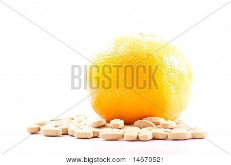 Naranja en montón de píldoras de vitamina C