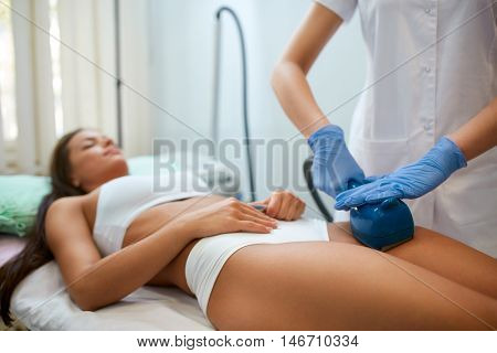 Young woman making a figure correction with professional device at spa clinic, deep oscillation causes the