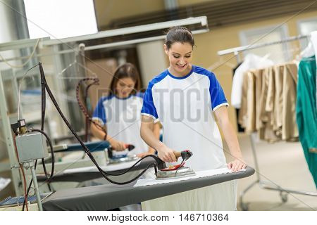 Smiling women iron textile on ironing board