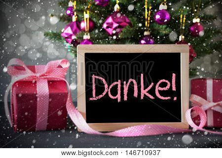 Chalkboard With German Text Danke Means Thank You. Christmas Tree With Rose Quartz Balls, Snowflakes And Bokeh Effect. Gifts Or Presents In The Front Of Cement Background.