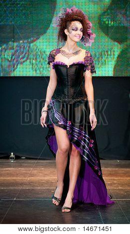 Model in purple walks the runway during