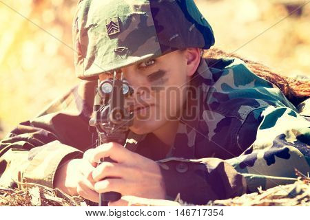 Army woman wearing camouflage holding gun
