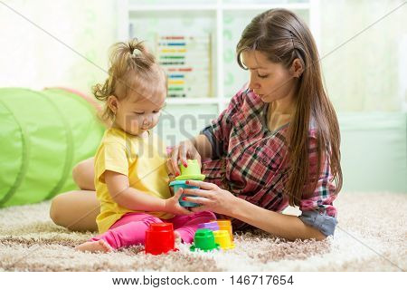 babysitter with kid girl playing in nursery