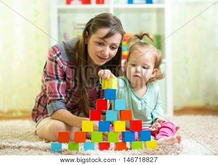 kid and mother build tower playing wooden toys at home or nursery