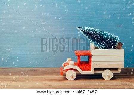 Christmas tree on toy truck car on wooden table. Christmas holiday celebration concept