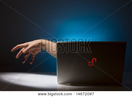 Hand Reaching Out From Unsecure Notebook