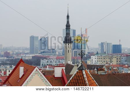 Tallinn, Estonia -March 27, 2010: Spire of town hall and roof of Tallinn old medieval city. Skyscrapers of new part of the city at background. Tallinn Estonia