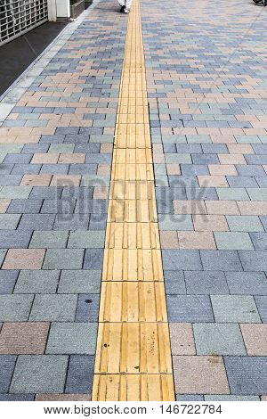 the yellow braille block on walkway in japan