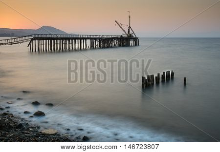 Seascape with old deserted industrial jetty with wooden poles in water during sunset at Karavostasi area near Leuka in Cyprus.