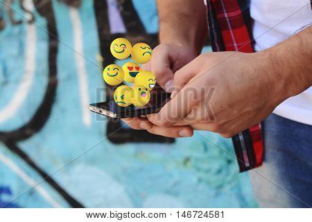 Young latin man using smartphone sending emojis. Social concept.
