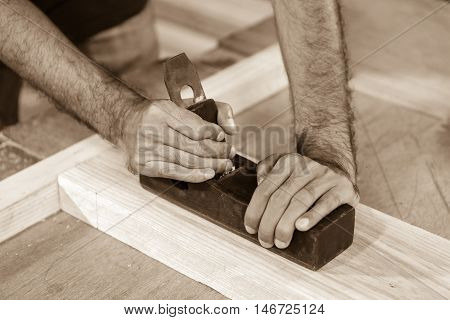 Skilled carpenter using a handheld plane to smooth and level the surface of a plank of hardwood close up view of his hands the tool and wood shavings