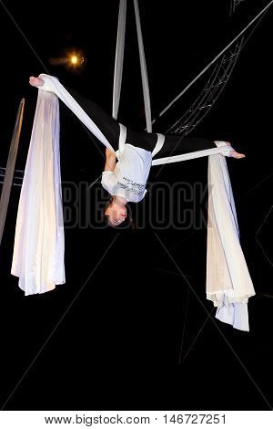 A teenage girl aerialist hangs upside down in a butterfly position before a drop.