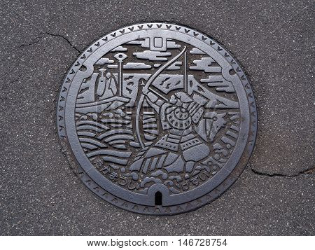 KAGAWA, JAPAN - JULY 21, 2016: A manhole cover in Takamatsu, Kagawa, Japan. Nasu no Yoichi, who particularly famous for his actions at the Battle of Yashima in 1184 was engraved on a manhole cover.