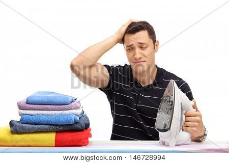 Sad guy scratching his head and looking at a pile of clothes for ironing isolated on white background