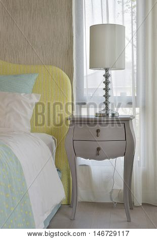 Classic style bedside table with reading lamp next to cozy style bedding with many style of green and yellow pillows