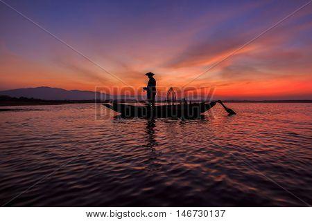 Silhouette of traditional fishermen throwing net fishing inle lake at sunrise time Myanmar