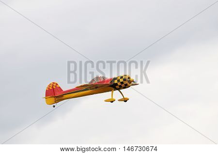 Flying propeller-driven model of airplane over gray cloudy sky
