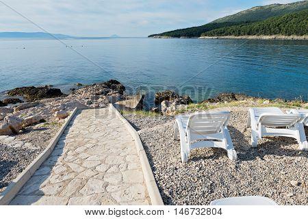 Walkway on the typical rocky beach in Istria, Croatian coast. Blue sea and sky.