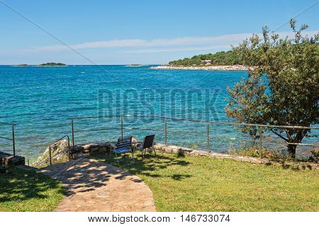 Typical rocky beach, two chairs and bue sea in Istria, Croatian coast