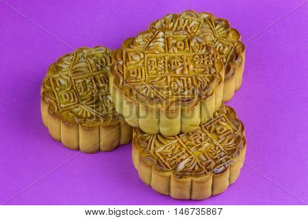 Traditional Chinese mooncakes stacked on a purple surface