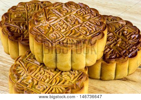 Chinese mooncakes stacked on a wooden table