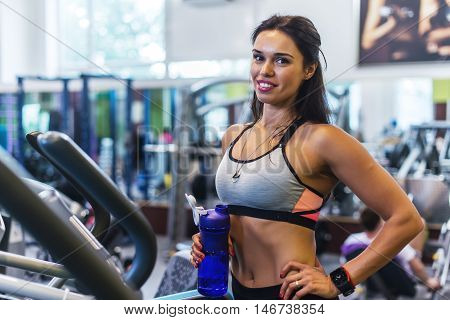 Woman exercising at the gym in an elliptical trainer Cardio training