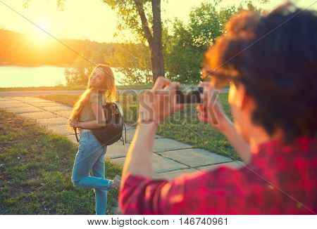 Happy joyful young couple taking photo on smartphone, walking in summer park together. Love, dating concept. Boyfriend takes pictures of his girlfriend outdoors
