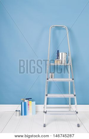 Painting the interior with tins and brushes on stepladder