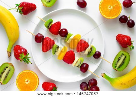 Fruit and berry skewers concept simple healthy raw meal and ingredients good for kids party top view