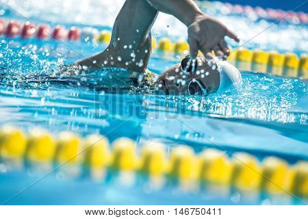 Amazing close-up photo of female swimmer in the motion in the swimming pool outdoors. She wears a black-lime swimsuit, a white swim cap and swim glasses. Horizontal.