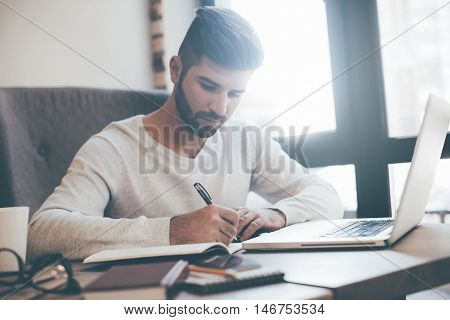 Concentrated on work. Confident young man writing something in notebook while sitting at his working place in office