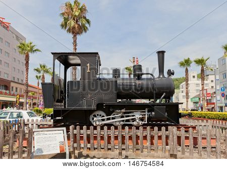 UWAJIMA JAPAN - JULY 22 2016: Steam locomotive Ke220 type on display outside Uwajima railway station Shikoku Island Japan. Made by Orenstein and Koppel OHG Company (Germany)