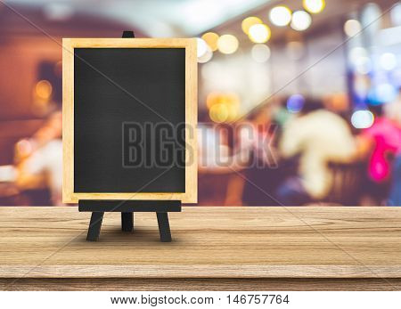 Blackboard Menu With Easel On Wooden Table With Blur Restaurant Background, Copy Space For Adding Yo