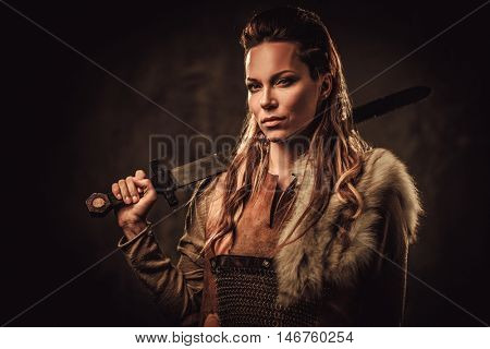 Viking woman with sword in a traditional warrior clothes.