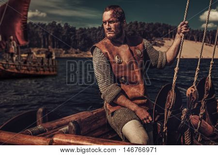 Confident viking man on Drakkar with forest on the background.