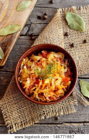 Spicy braised cabbage in a bowl and on old wooden background. Cabbage braised with carrots, tomatoes and garlic and garnished with a sprig of dill. Vegetable recipe