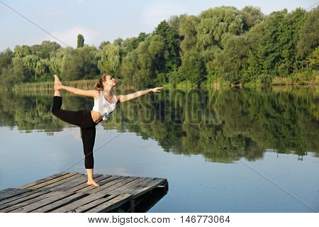 Young beautiful woman engaged in yoga on the river bank, Asana on balance Nataraja asana